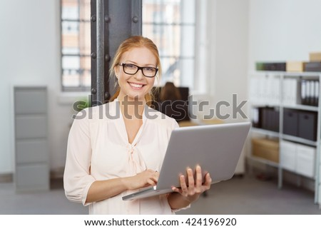 Waist Up Portrait of Smiling Young Businesswoman with Red Hair and Glasses Holding Laptop Computer While Leaning Against Pole in Spacious Open Concept Modern Office - stock photo