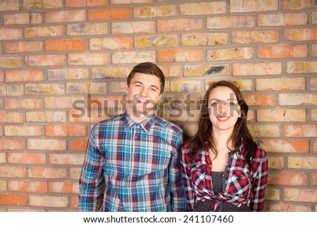 Waist Up Portrait of Smiling Young Couple Wearing Plaid Shirts Standing Together in front of Brick Wall - stock photo