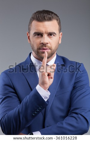Waist up portrait of successful young business worker is asking for silence. He is standing and looking at camera with seriousness. The man is raising finger to his mouth. Isolated on grey background - stock photo