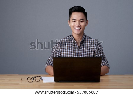 Waist-up portrait of talented Asian designer distracted from work in order to pose for photography, gray background