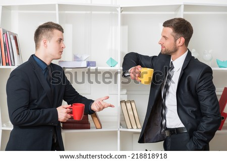 Waist-up portrait of two handsome businessmen in suits looking on each other while having a coffee-break in office standing near a bookshelf and discussing something - stock photo