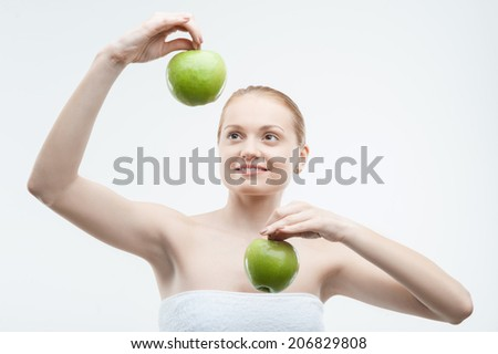 Waist up portrait of young attractive smiling woman in towel playing with two green apples, isolated on white - stock photo