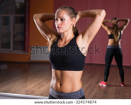 Waist Up Portrait of Young Blond Female Dancer Wearing Exercise Clothing Standing in Dance Studio with Hands Behind Head and Reflection in Mirrored Wall - stock photo