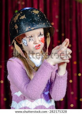 Waist Up Portrait of Young Blond Girl Wearing Clown Make Up and Military Helmet Making Gun Out of Clasped Hands and Aiming with Squinted Eyes - stock photo