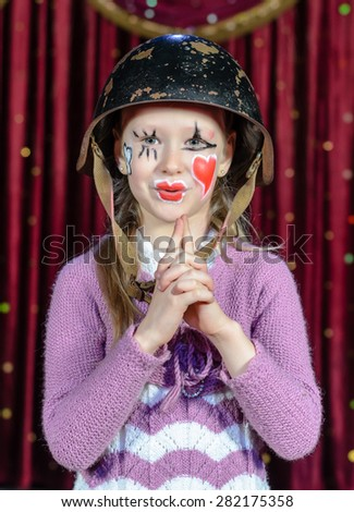 Waist Up Portrait of Young Blond Girl Wearing Clown Make Up and Military Helmet Making Gun Out of Clasped Hands and Blowing Imaginary Smoke from Barrel - stock photo