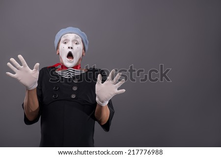 Waist-up Portrait of young male mime confused breeding his hands showing that he is scared and frighten looking at you with wide opened mouth and eyes isolated on grey background with copy place - stock photo