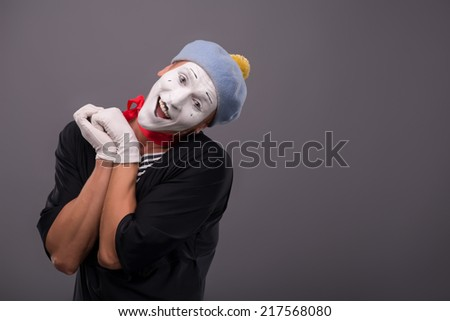 Waist-up Portrait of young male mime holding hands near his face like a girl and playfully looking at the camera and happy smiling isolated on grey background with copy place - stock photo