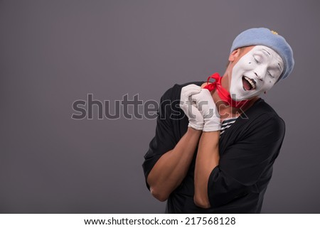 Waist-up Portrait of young male mime holding hands near his face like a girl and playfully looking down and happy laughing isolated on grey background with copy place - stock photo