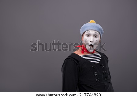 Waist-up Portrait of young male mime with white face, grey hat opening his mouth and looking aside with astonishment isolated on grey background with copy place - stock photo