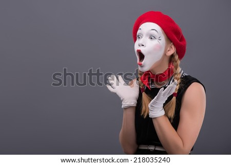 Waist-up portrait of young mime girl with red hat and red scarf looking aside with pleasant surprise, showing that she is happy to see something, isolated on grey background with copy place - stock photo
