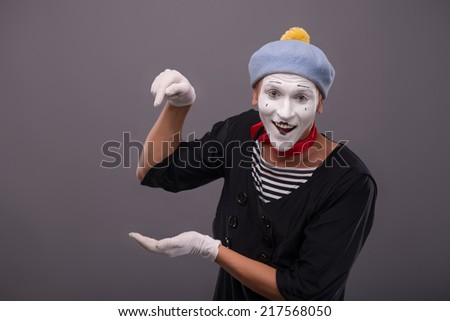 Waist-up Portrait of young mime holding something in one his hand and showing there with finger of another hand, happy looking at the camera isolated on grey background with copy place - stock photo