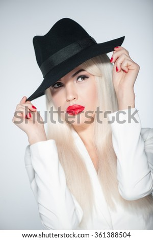 Waist up portrait of young sexy woman with black hat and white wig. She is standing and staring at camera secretly. Isolated - stock photo