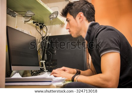 Waist Up Profile of Young Attractive Man with Dark Hair, Sitting at Computer Desk Working on Paper Homework or on His Start-up Business, in Dorm Room - stock photo