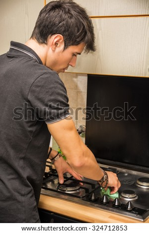 Waist Up Rear View of Attractive Young Man with Dark Hair, Cleaning Surface of Stove Top in Kitchen with Sponge - Responsible Man Doing Housework, in First Apartment