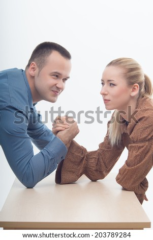 Waistup portrait of a young attractive woman and man fighting on hands isolated on white background - stock photo
