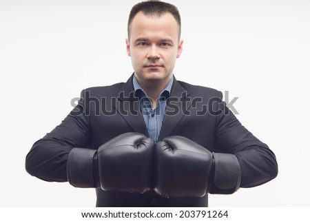 Waistup portrait of young handsome serious businessman in black boxing gloves isolated on white background - stock photo