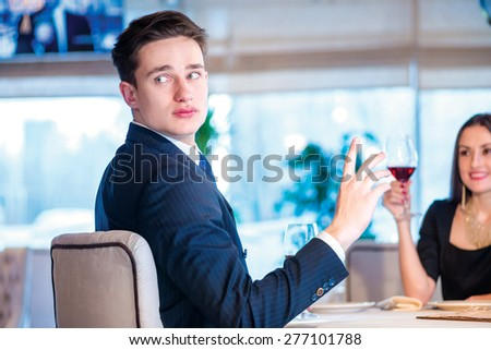 Waiter account. Romantic dinner in the restaurant. Young couple sitting at a table at each other and smiling lovingly at the restaurant while toasting with wine. - stock photo