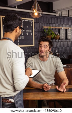 Waiter and customer talking in a coffee shop - stock photo