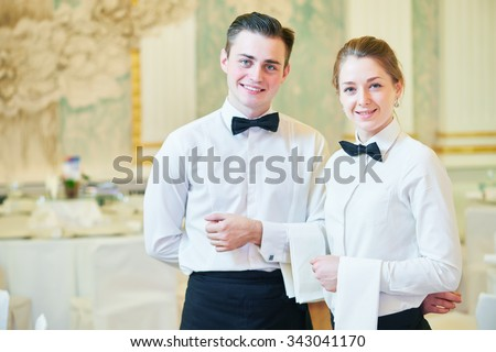 waiter and waitress occupation. Young man and woman at catering service in restaurant during event - stock photo