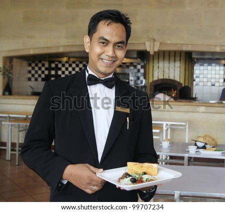 waiter at restaurant holding food - stock photo