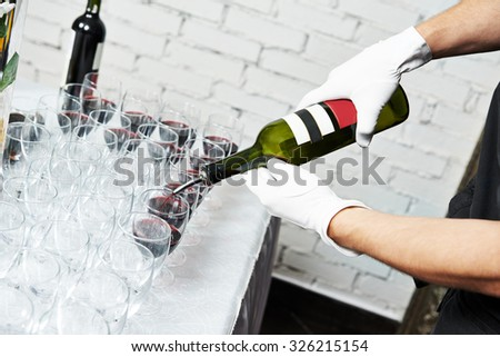 Waiter bartender pouring red wine into glasses at party event - stock photo