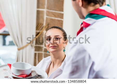 waiter brings a dish for a nice woman at the restaurant, she looks at camera and smiles - stock photo