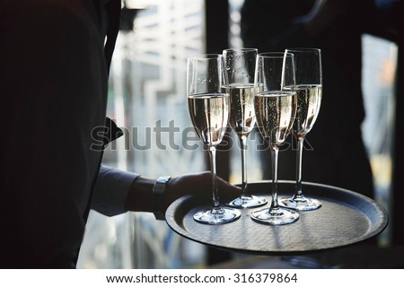 waiter brings glasses of champagne on a tray - stock photo