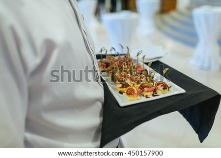 Waiter cares a plate with tasty appetizers - stock photo