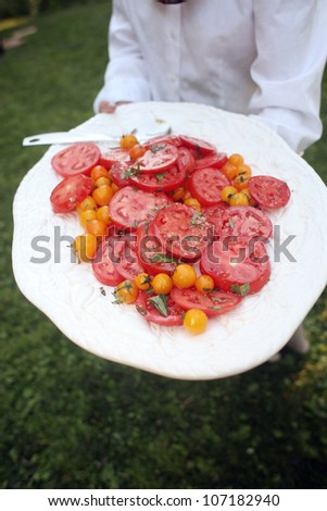 Waiter Carrying a Plate of Organic Heirloom Tomatoes - stock photo