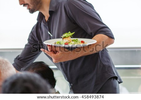 Waiter carrying a plate with salad dish on a wedding