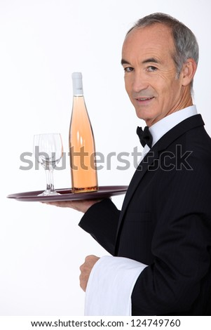 Waiter carrying bottle of wine on tray - stock photo