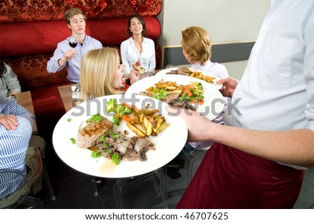 Waiter carrying plates with food, serving the customers of a restaurant - stock photo