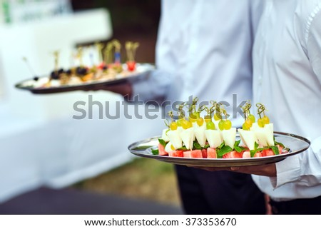 Waiter carrying plates with meat dish on some festive event - stock photo