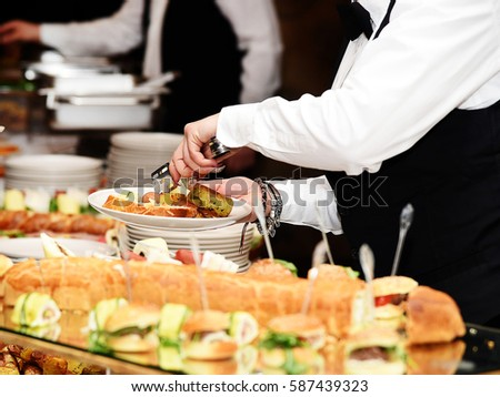 Waiter carrying plates with potato vegetable dish on some reception event, party or wedding party