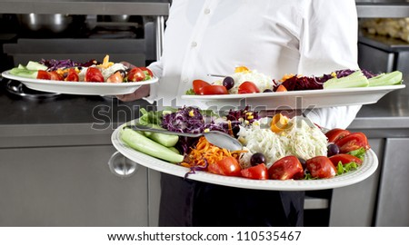Waiter carrying plates with salad
