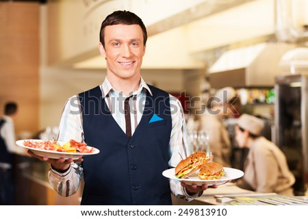 Waiter carrying two plates with sandwich. man looking into camera and holding breakfast