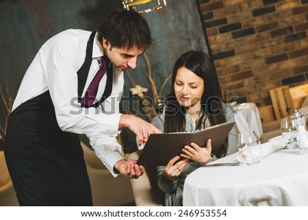 Waiter explaining the menu to a young woman - stock photo