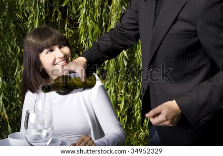Waiter filling a glass of white wine for a woman dining in a garden