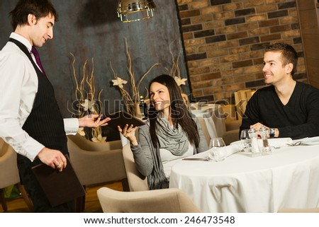 Waiter giving menu to a young couple