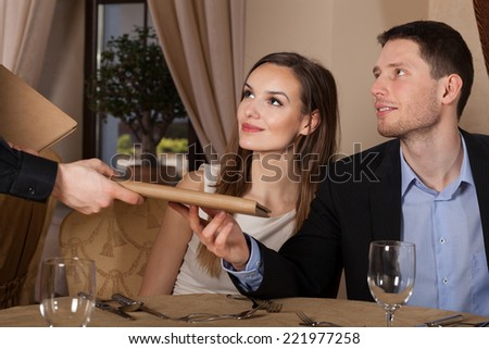 Waiter giving menu young couple in restaurant - stock photo