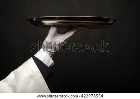 Waiter hand holding tray over black background.