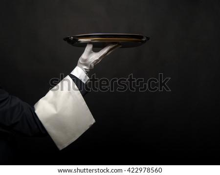 Waiter hand holding tray over black background. - stock photo