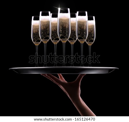 waiter hand with champagne on black background - stock photo