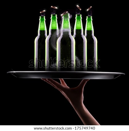 waiter hand with open wet beer bottles on a tray - stock photo
