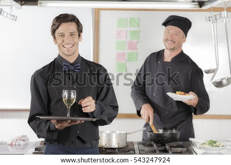 Waiter holding a glass of wine and receiving his next order from the cook in industrial kitchen wearing black uniform