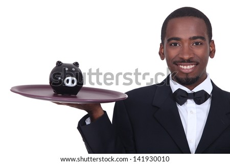 Waiter holding a piggy bank on his tray - stock photo