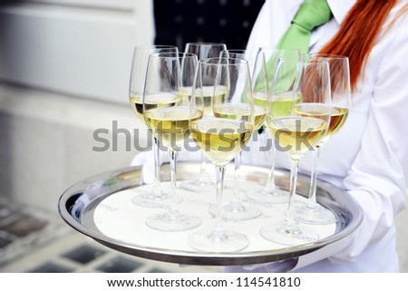 waiter holding a tray with glasses of white wine - stock photo