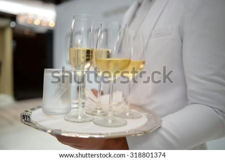 Waiter holding a tray with glasses of wine at party - stock photo
