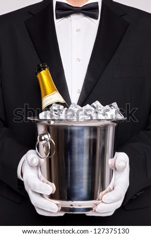 Waiter holding a wine cooler with a bottle of Champagne on ice - stock photo