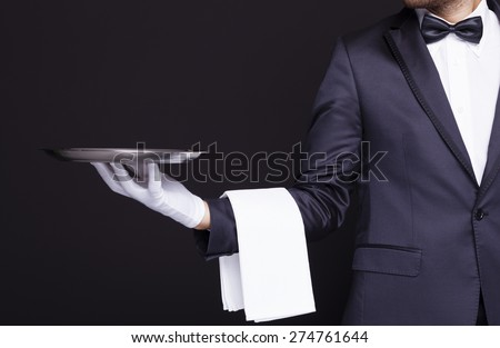 Waiter holding an empty silver tray against dark background